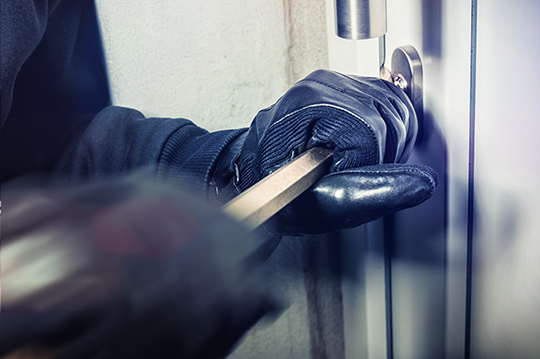 Einbrecher, der Handschuhe trägt, bricht Eingangstür mit Brecheisen auf