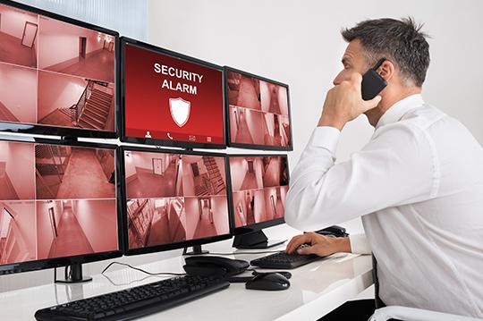 Security Agent in Sicherheitszentrale wird über Einbruch alarmiert