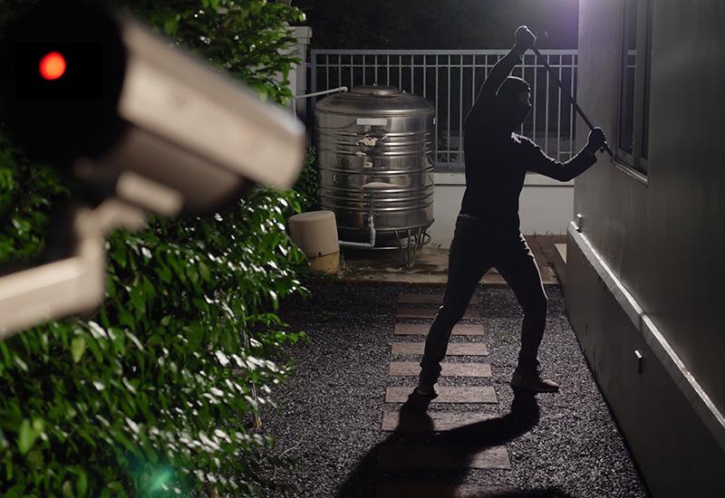 Einbrecher in der Nacht, der versucht ein Fenster aufzubrechen